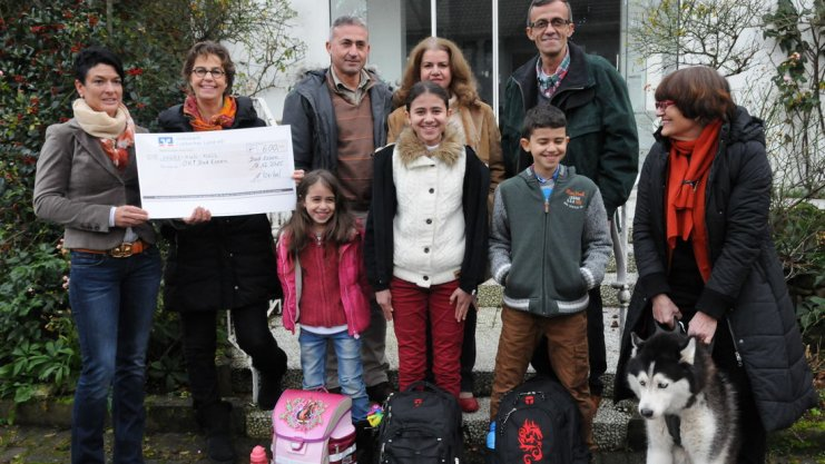 Über ihre neuen Schulranzen freuen sich Lugen, Sedra und Adel mit ihrer Familie, Andrea Keibel (links), die den Scheck mitgebracht hatte, Viktoria von dem Bussche und Frauke Weiss.